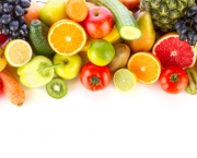 A pile of fresh, healthy fruits and vegetables on white.